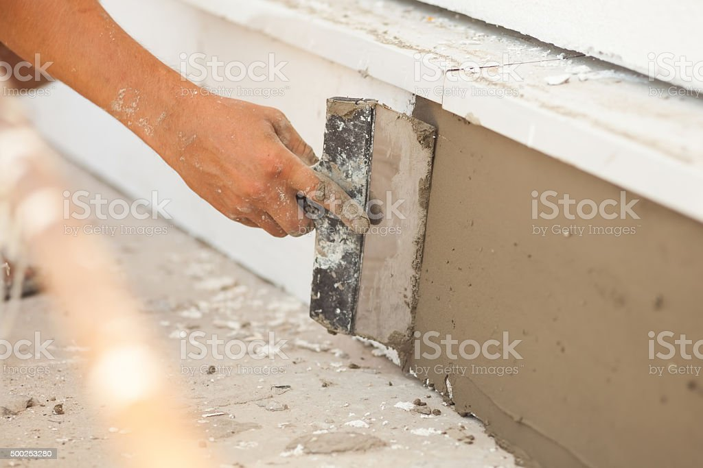 Man hand with trowel plastering a foundation of house stock photo