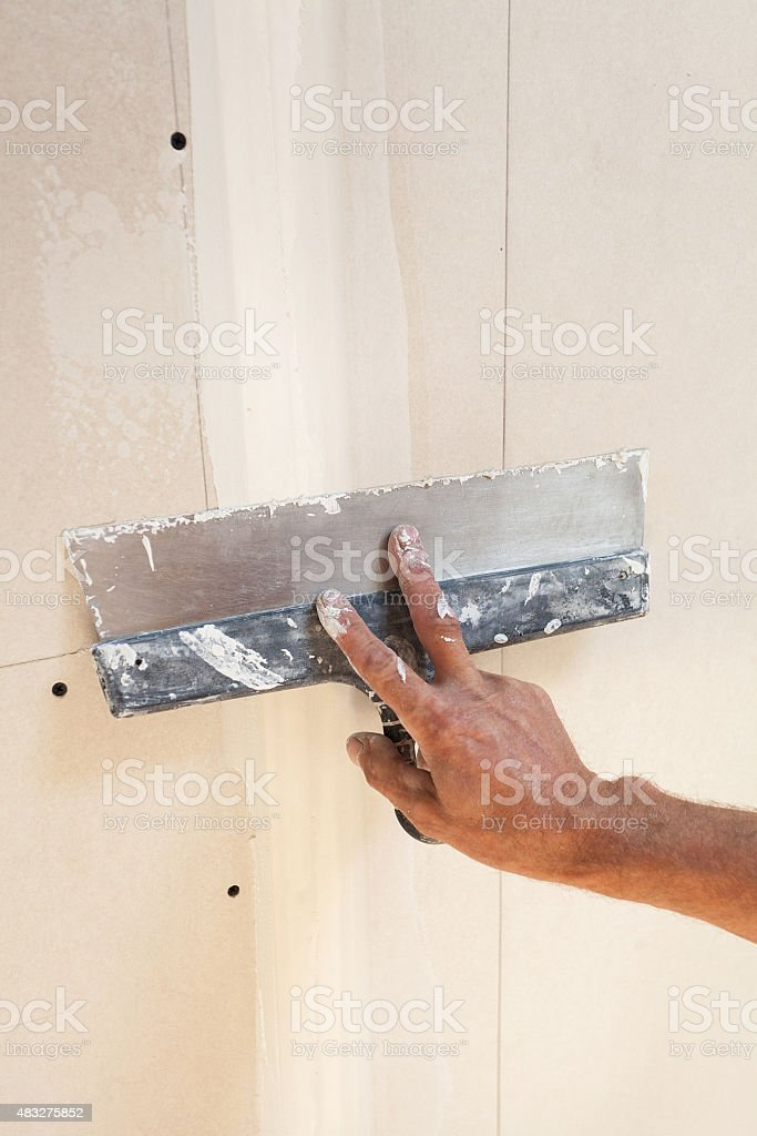 Man hand with trowel plastering a plasterboard stock photo