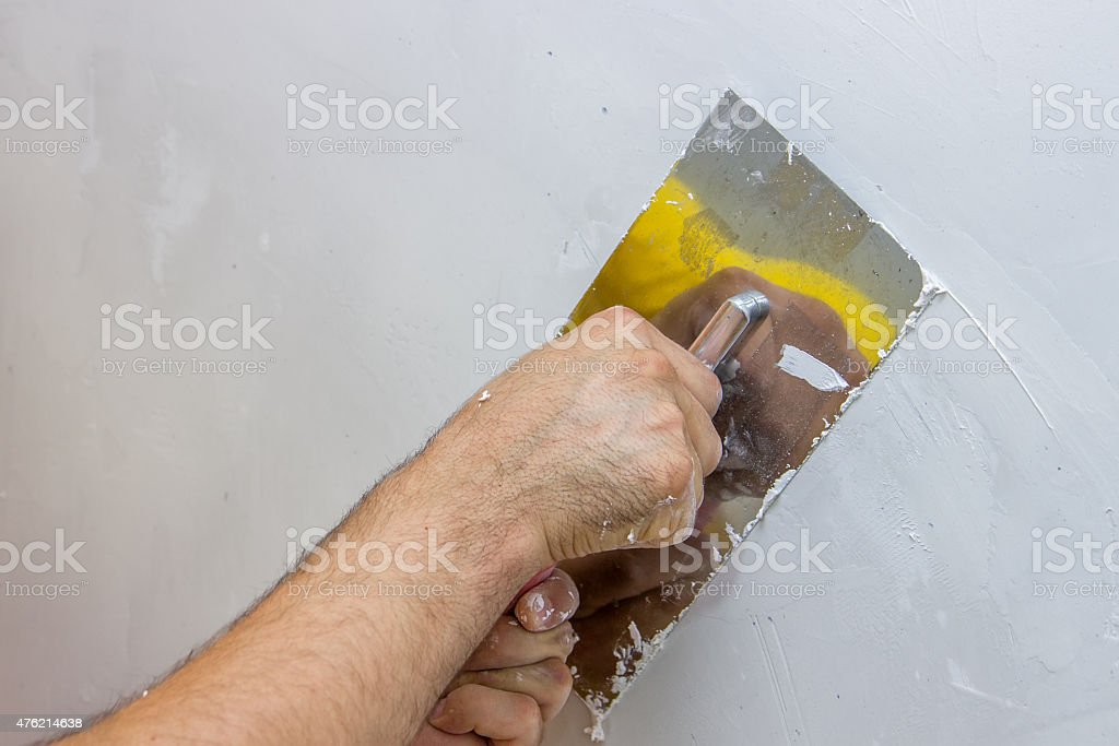 man hand with trowel plastering a wall 4 stock photo