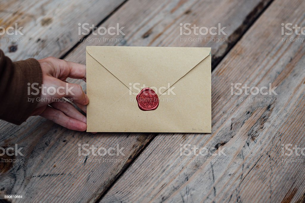 Man hand with wax seal envelope on wooden background stock photo