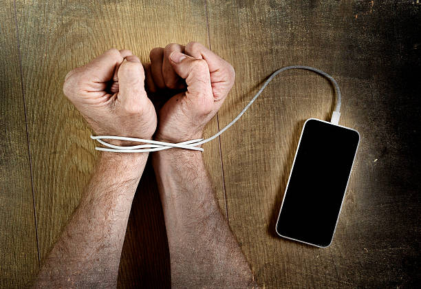man hand wrists wrapped  with mobile phone cable handcuffed stock photo