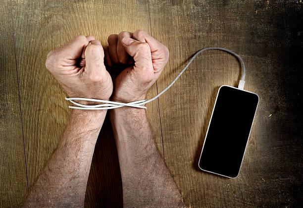 homem mão pulsos enrolado com telefone móvel handcuffed a cabo - atado - fotografias e filmes do acervo