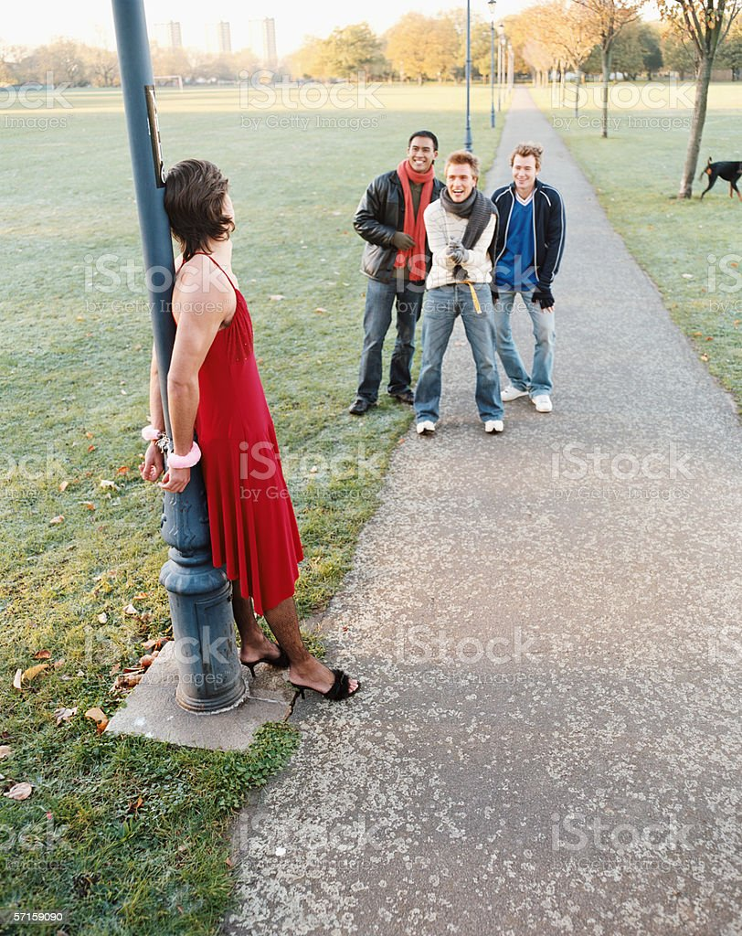 Man handcuffed to lamp post being laughed at stock photo