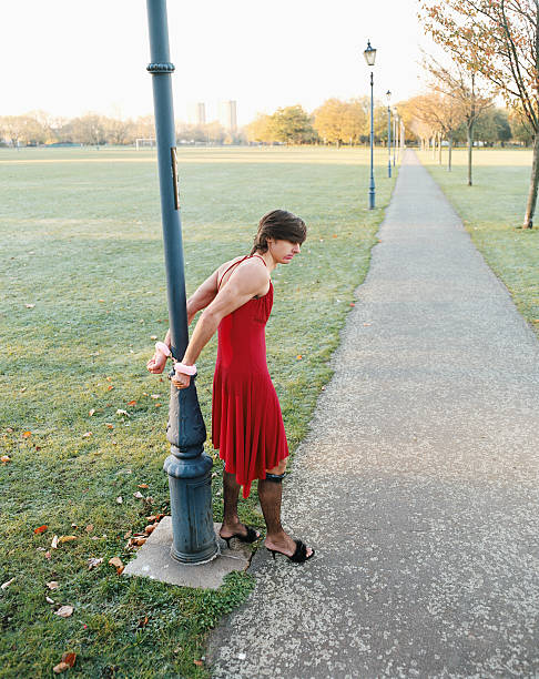 Man handcuffed to lamp post wearing red dress stock photo