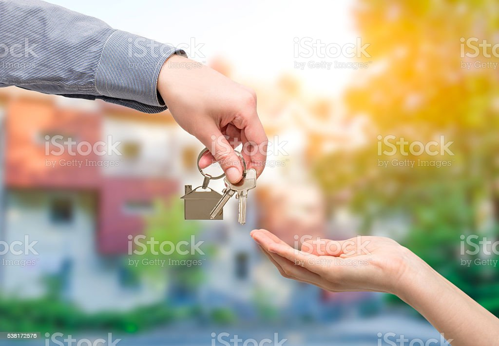 Man handing a house key to woman. Real estate concepts. stock photo