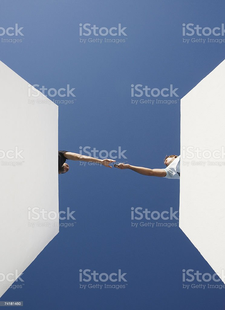 Man handing cell phone to man from below royalty-free stock photo