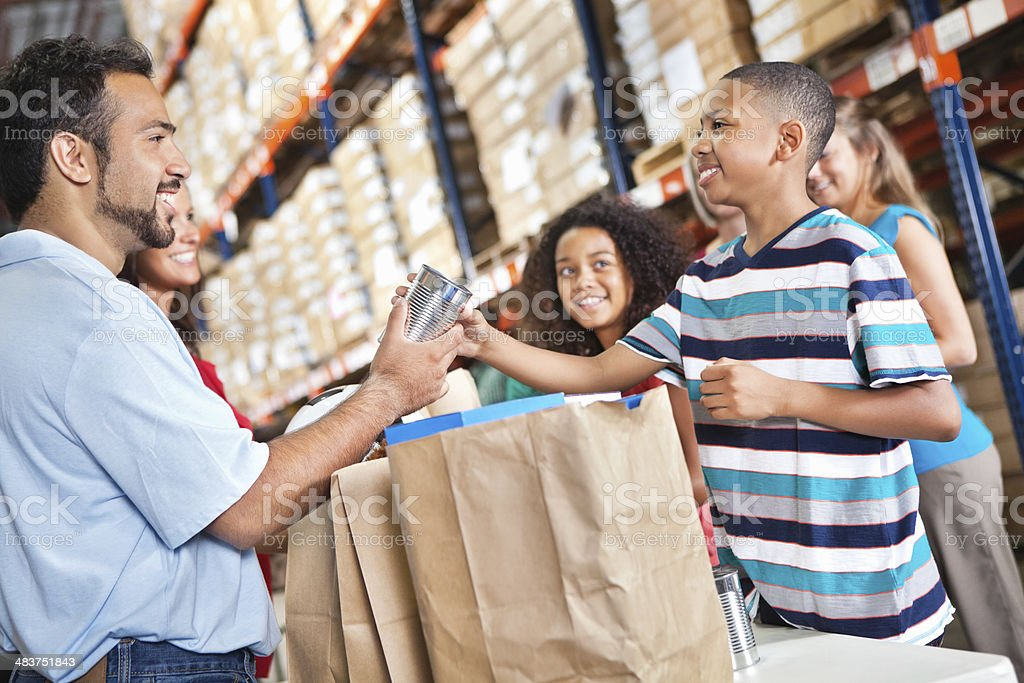 Man handing food parcels to young boy in warehouse royalty-free stock photo