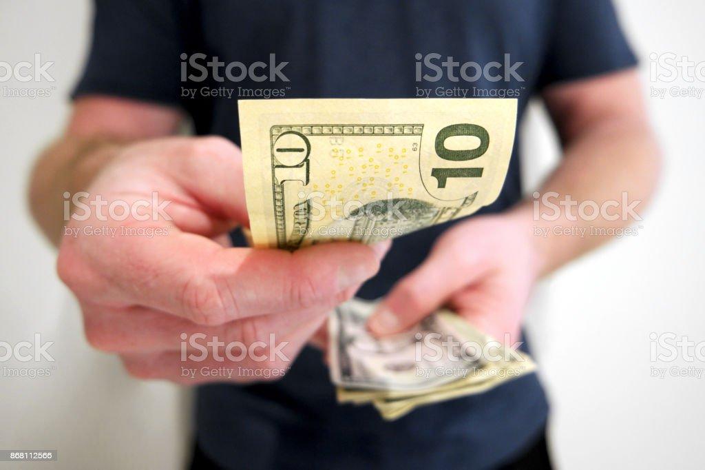Man handing out american ten dollar bill stock photo