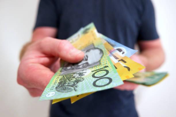 Man handing out hundreds and fifties Australian dollar bills stock photo