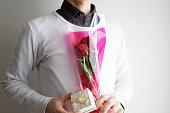 赤いバラを手渡す男