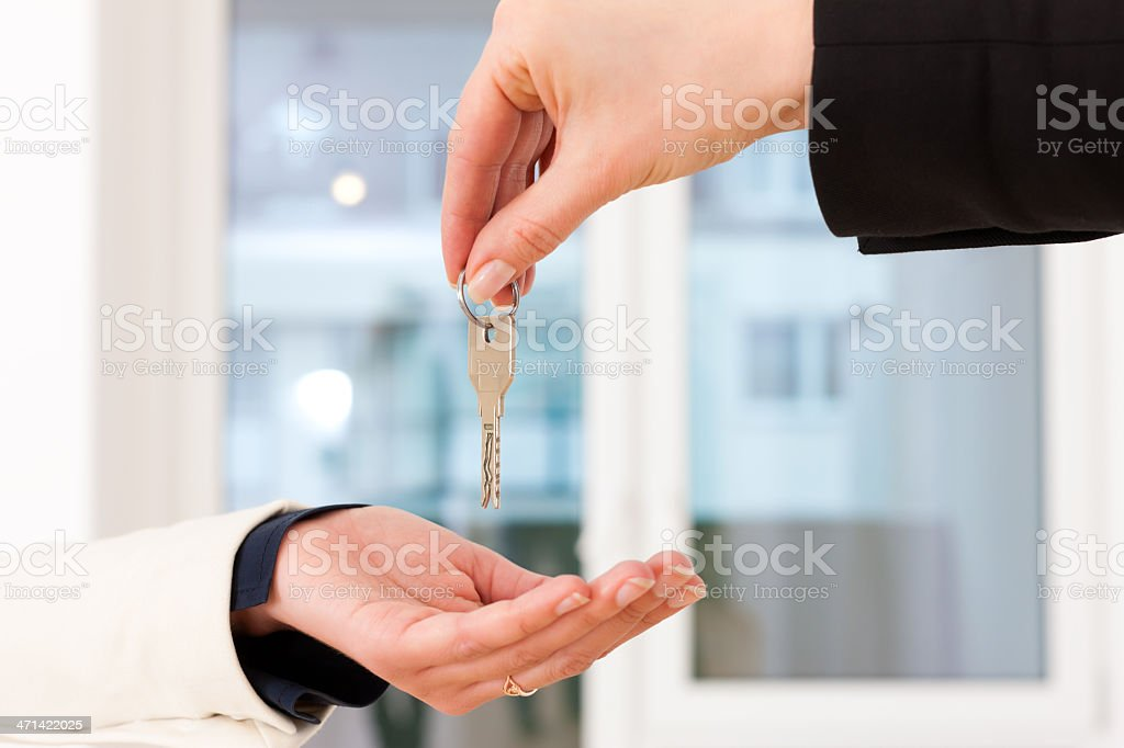 A man handing over keys to a woman to get new apartment royalty-free stock photo
