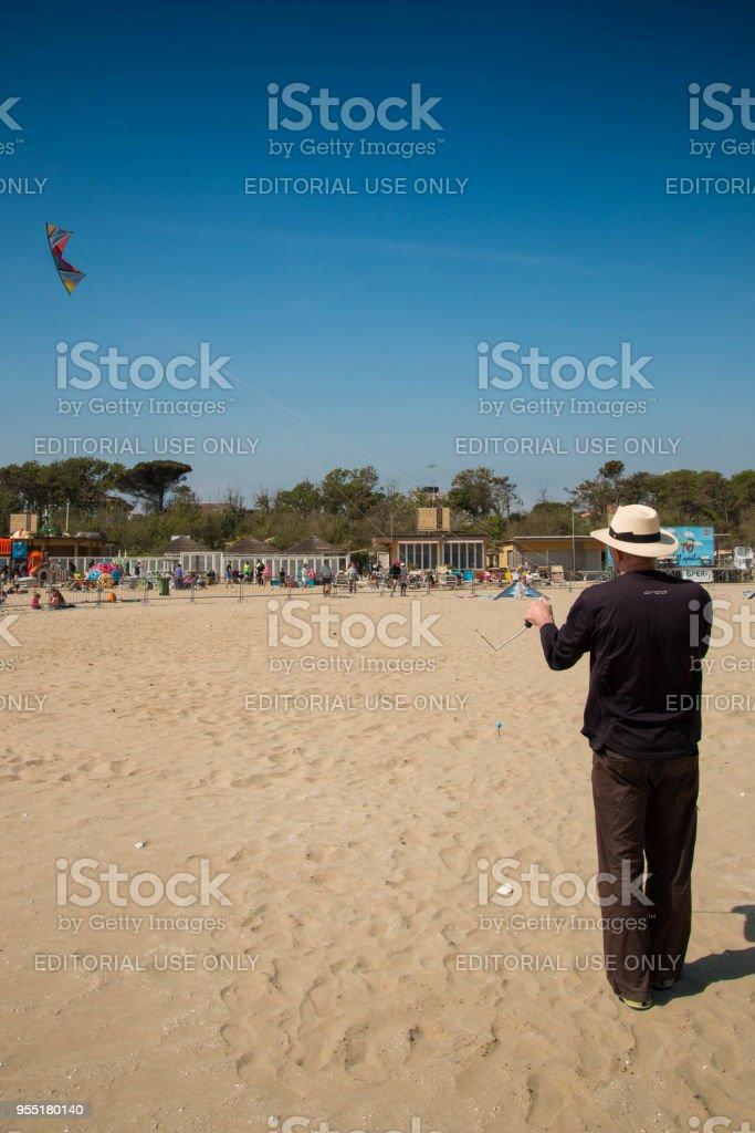A man handling his kite on the beach at Cervia international kite festival 'Artevento' 2018. stock photo