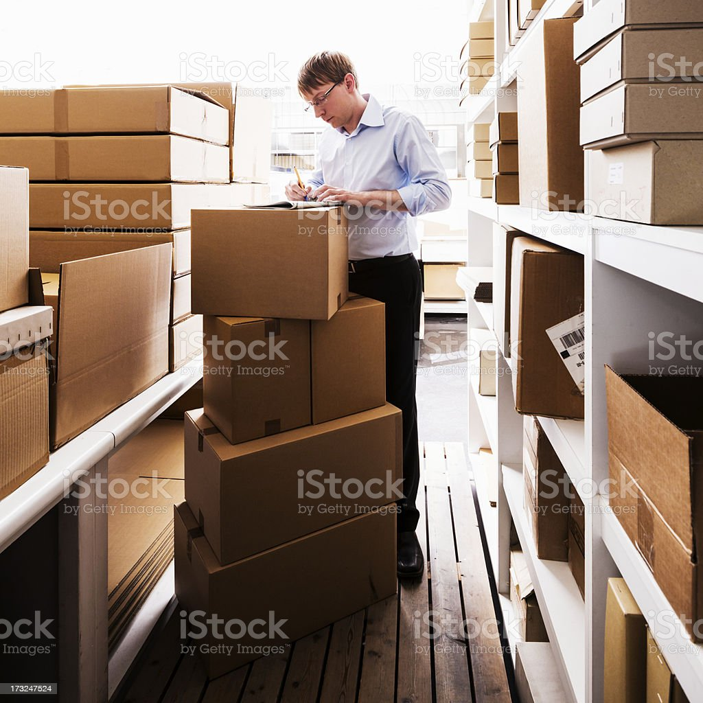 Man handling paperwork in a warehouse royalty-free stock photo