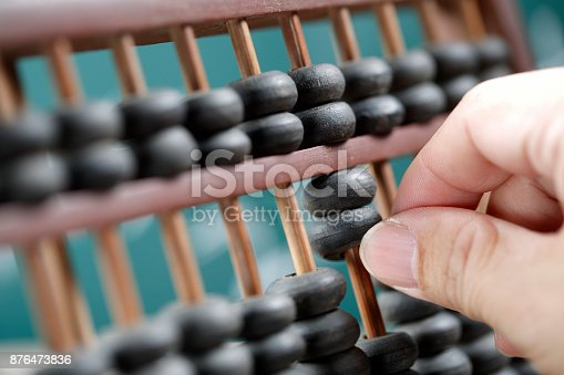 istock Man hands are operating abacus 876473836