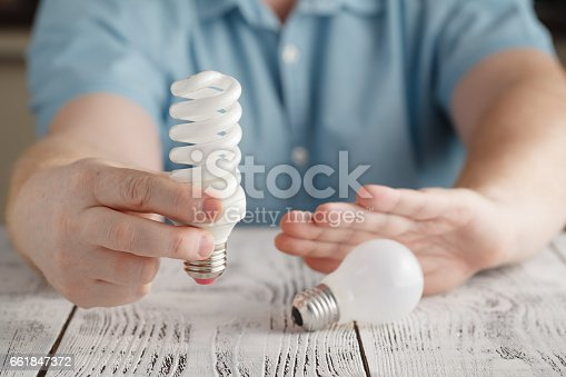 istock Man hands decline glow-lamp and hold spiral lamp against wooden table. Man hold lamps in hands. Energy efficiency concept. 661847372