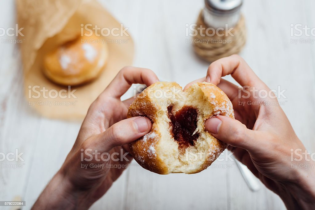Man hands eating Bismarck donut with coffee on wooden table stock photo