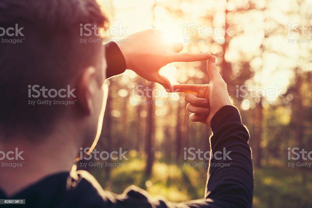 Man hands framing far sunlight stock photo