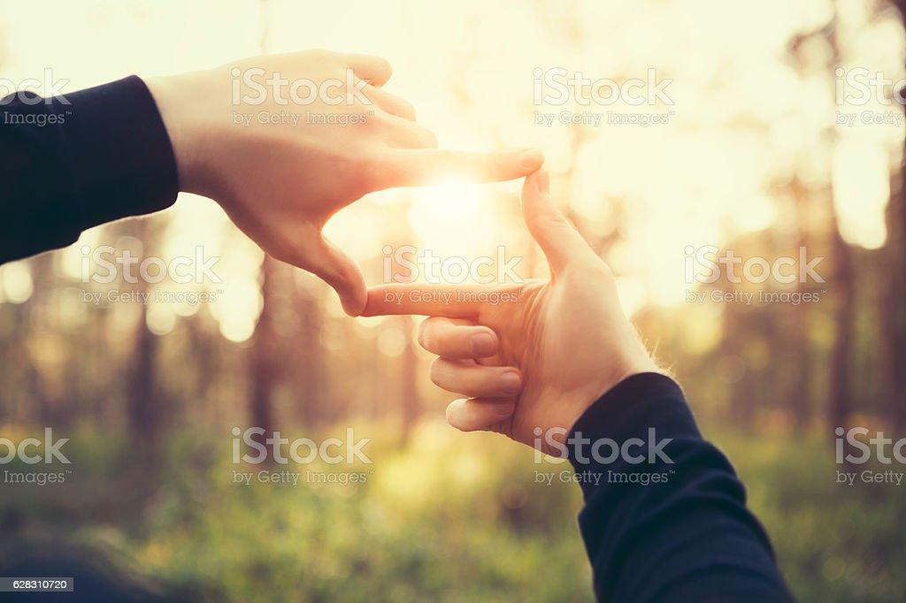 Man hands framing far sunlight – zdjęcie
