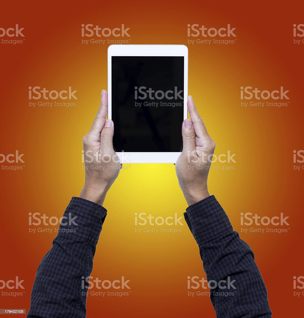 Man hands hold digital tablet isolated on orange background royalty-free stock photo