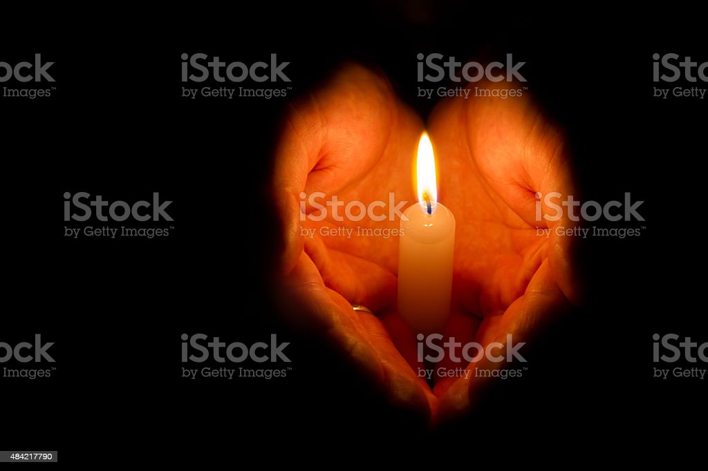 Religious concept. Man hands holding a burning candle on dark...