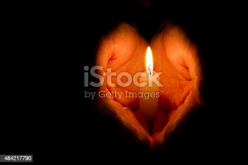Religious concept. Man hands holding a burning candle on dark background