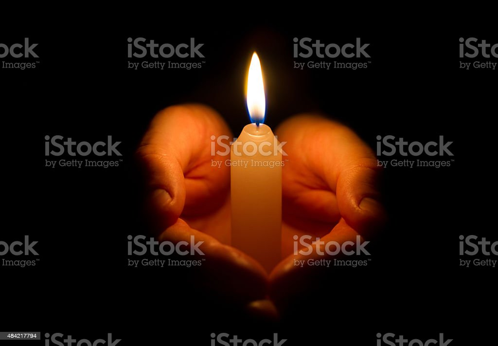 Man hands holding a burning candle stock photo