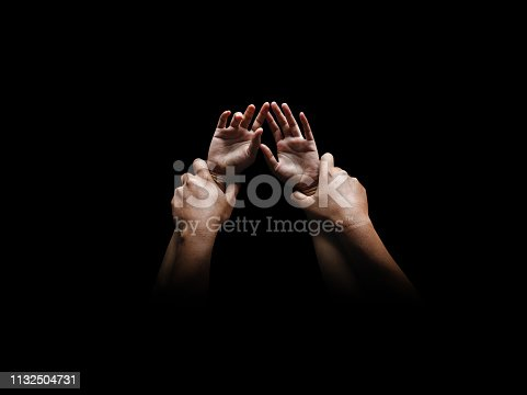 Man hands holding a woman hands for rape and sexual abuse concept isolated on black background