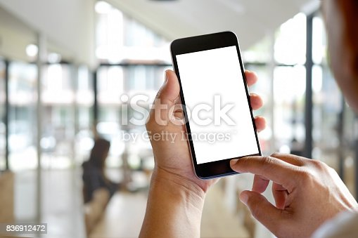 istock Man hands holding blank screen a smartphone and blurred background. 836912472