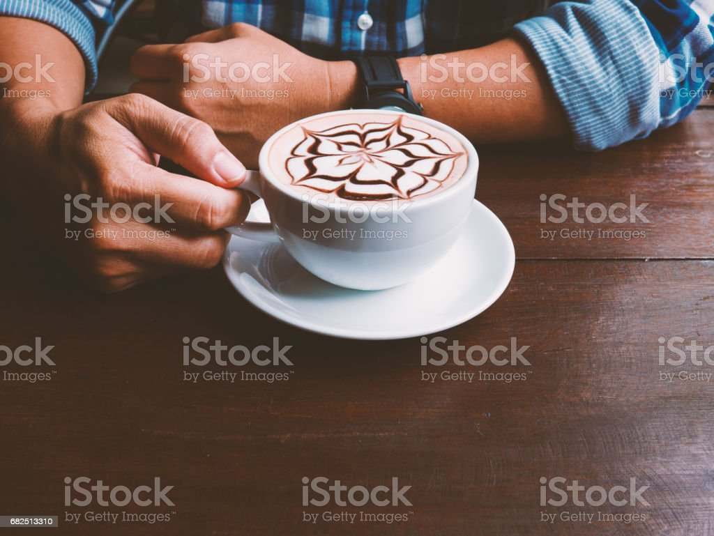 Man hands holding coffee cup of latte art on wooden table at cafe. Selective focus and vintage tone. Copy space. Стоковые фото Стоковая фотография