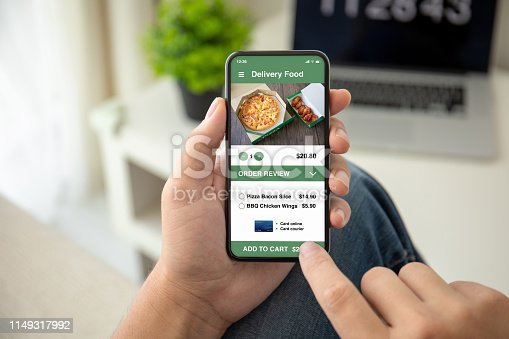 man hands holding phone with app delivery food on the screen in the house in room