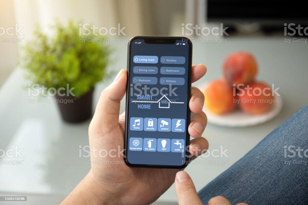 Ein Mann die Hände halten Telefon mit app smart Haus im Zimmer nach Hause – Foto