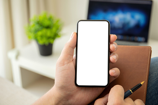man hands holding phone with isolated screen in the house in room