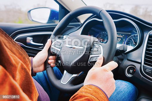 Washington DC, USA - May 1, 2015: Man hands holding the steering wheel of Chrysler car