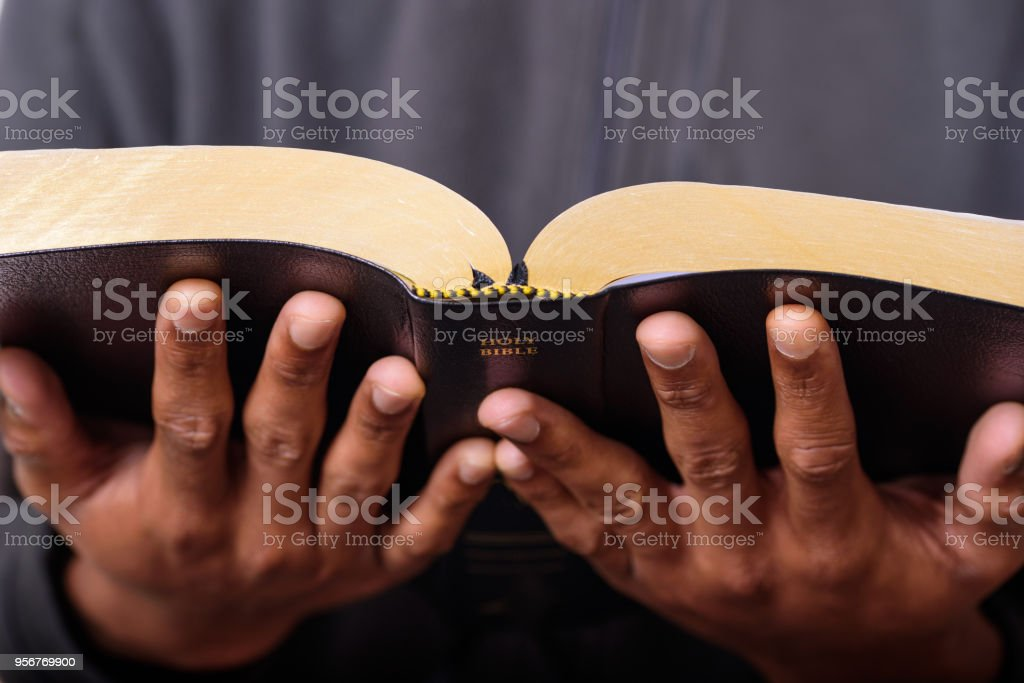 A Man Hands Holding The Holy Bible stock photo