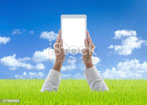 899410700 istock photo Man hands holding white digital tablet on green grass 477963863