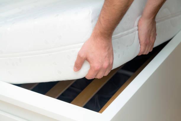 Mann die Hände heben die Matratze im Schlafzimmer. Mit Blick auf den Bettrahmen, inspiziert die Matratze – Foto