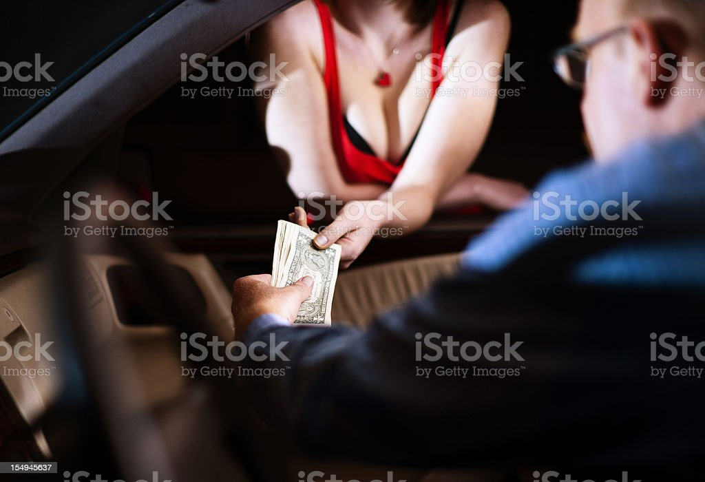 Man hands money to hooker through car window stock photo