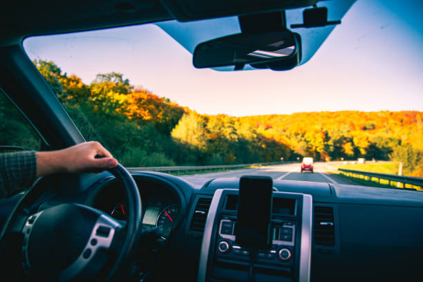 man hands on steering wheel riding by autumn speedway fall season stock photo