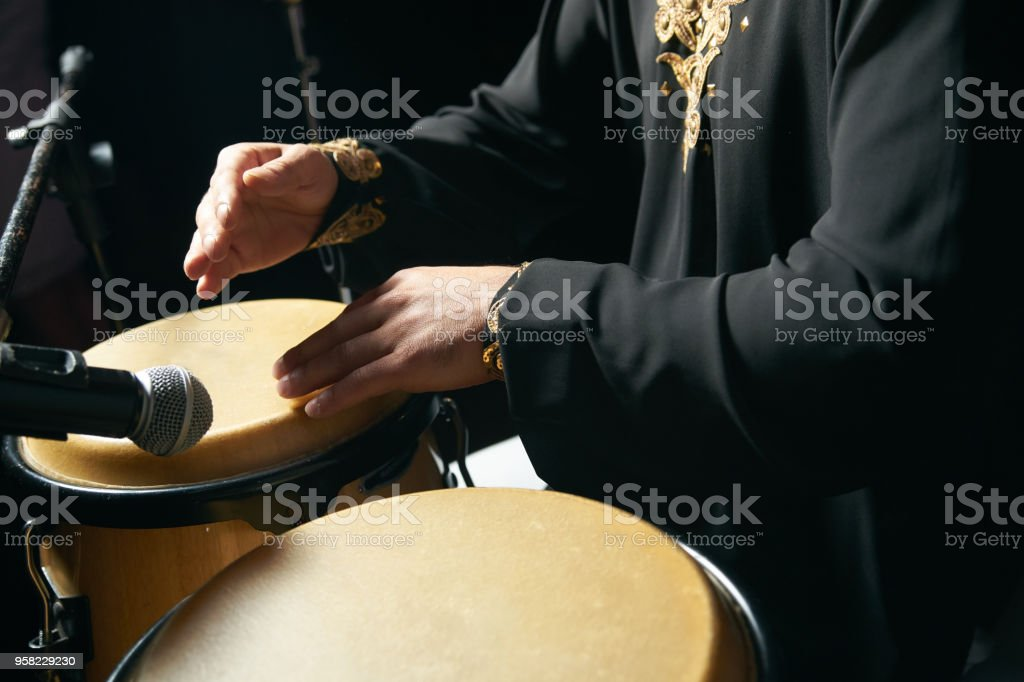 Man hands playing music at djembe drums stock photo