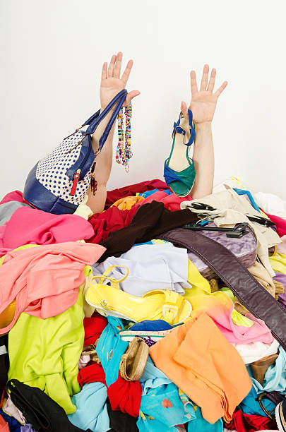 Man hands reaching out from a big pile of clothes. stock photo