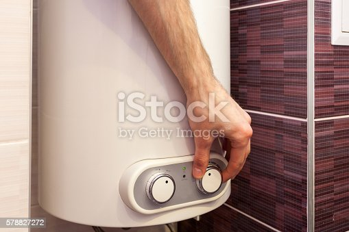 996279800istockphoto Man hands setting the temperature of water in Electric Boiler 578827272