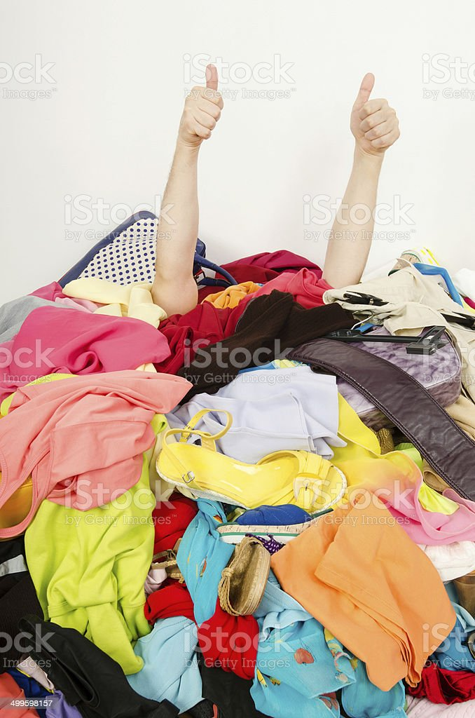 Man hands signing thumbs up under big pile of clothes. stock photo