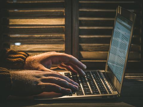 Man hands typing in MacBook Air Laptot beside wooden window