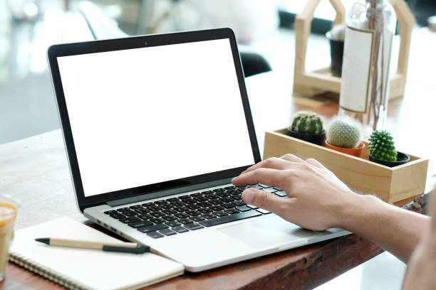 Man hands typing laptop computer with blank screen for mock up while sitting in the cafe, technology and lifestyle concept stock photo