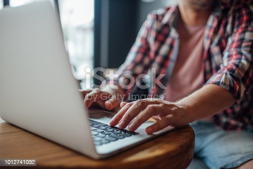 879813798istockphoto Man hands typing on a laptop keyboard on a desk 1012741032