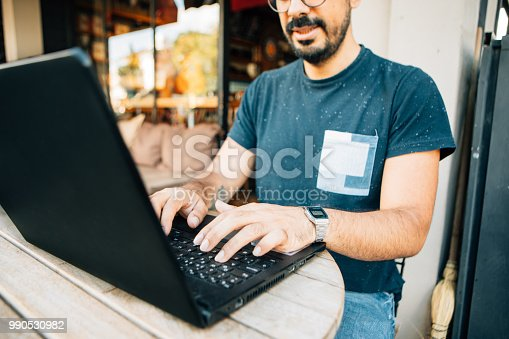 879813798istockphoto Man hands typing on a laptop keyboard on a desk 990530982