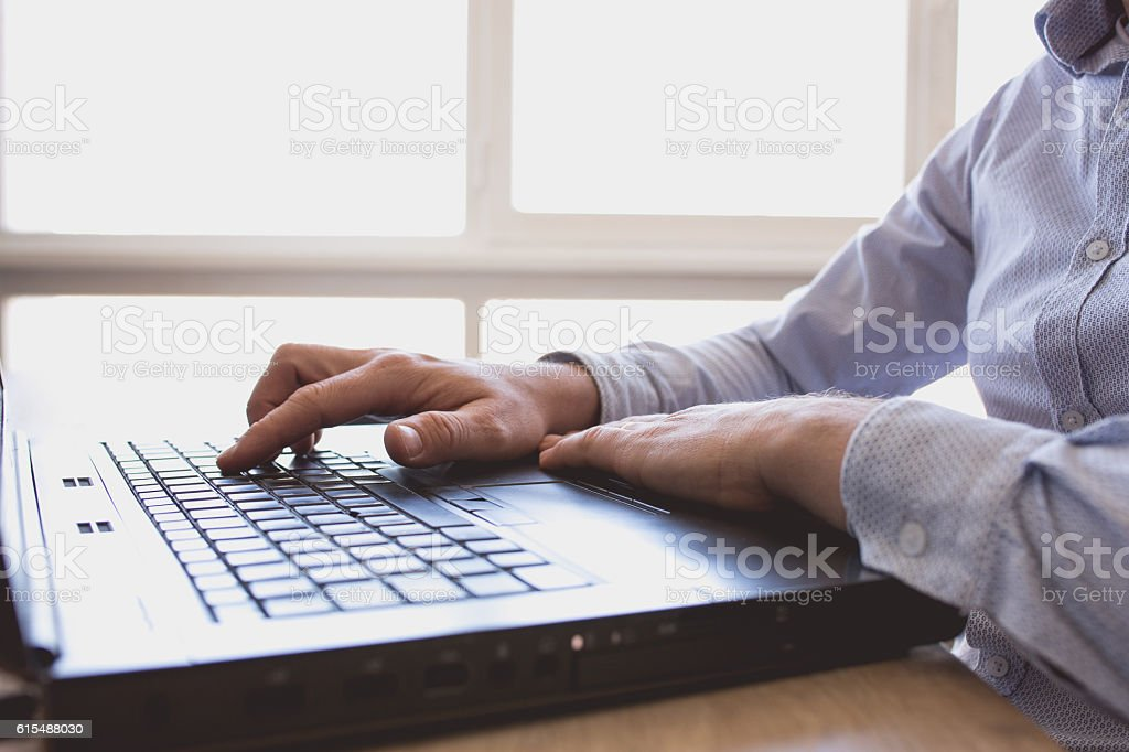 Man hands typing on keyboard laptop stock photo