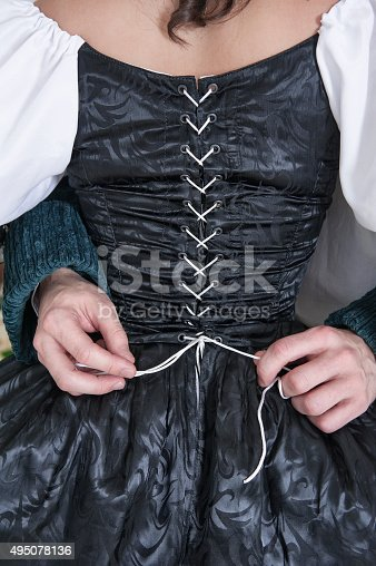 Man hands untying corset of woman in black medieval dress