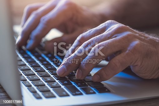 879813798istockphoto Man hands using laptop computer 1006517984