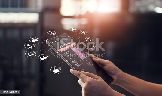 istock Man hands using online banking and icon on tablet screen device in coffee shop. Technology E-commerce Commercial. Online payment digital and shopping on network connection. 973139084